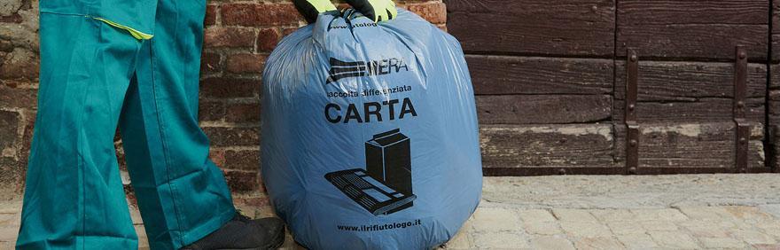 foto di un operatore che raccoglie un sacco per la raccolta differenziata della carta
